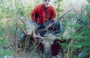 This hunter is posing with his kill before getting to the hard work as he does not have much time; the meat can be ruined if the
