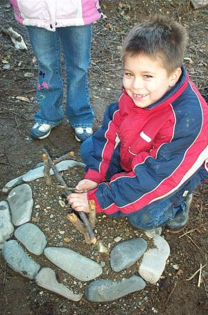 This child is learning to make a fire without matches.