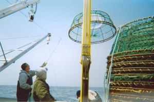 As you can see the boom arm is assisting the fishermen in unstacking the traps one by one.