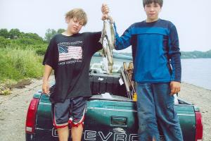 These young boys are proud with their catch of the day, lots of trout to feed their families.