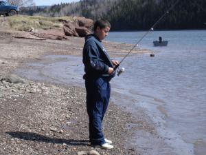This young man is holding his rod waiting for trout to grab his bait.