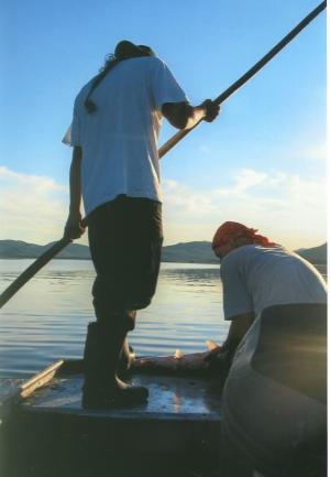 These two men are checking their nets and have caught one salmon so far.