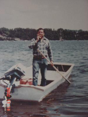 In this picture, the man is holding a pole that is used to push the boat out into deeper parts of the water.