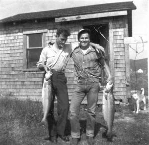Both fishermen are holding up their salmons proudly; they are large enough to feed a few families.