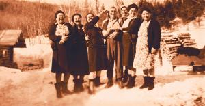 Six women and a man posing for a picture outside in the snow infront of newly cut firewood.
