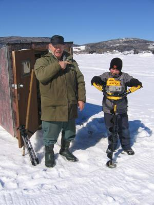 The young boy is using an auger to make holes in the ice so they can fish for smelts.