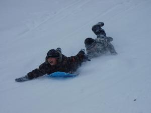 There are many ways to slide down a steep hill. Both boys are laying face forward.
