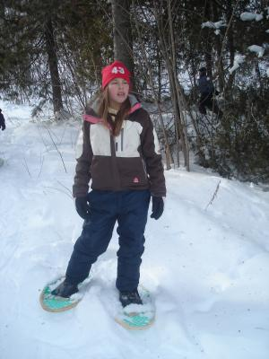 This youth is learning about the significance of snow shoes in the winter and how they can also be fun.